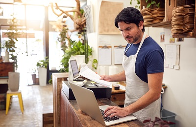 Image of business owner working with laptop in store